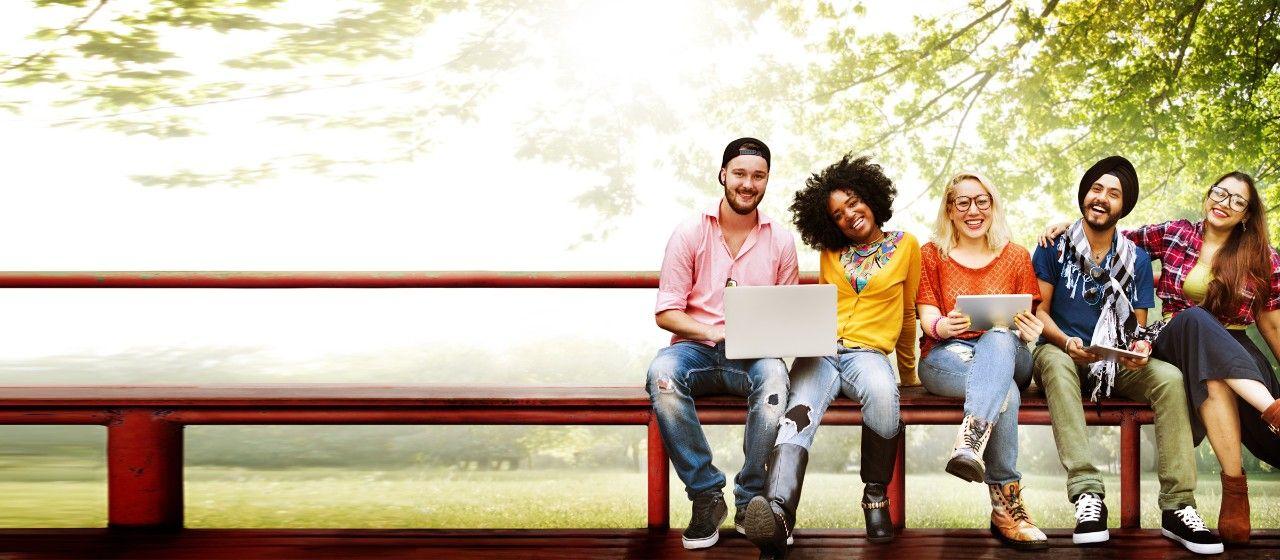 Junge Leute sitzen auf der Parkbank.